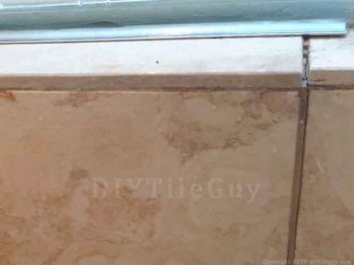 cracked grout joints from water damage. travertine tiles