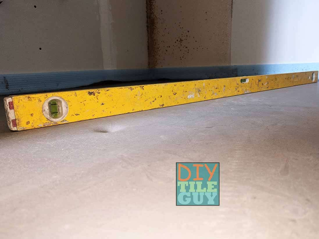 Checking a self-leveling pour with a level